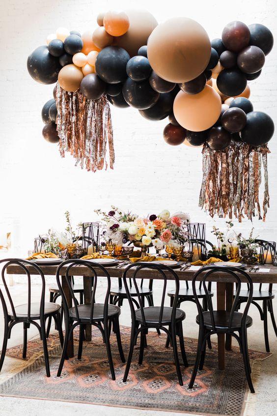 a gorgeous Halloween bridal shower reception with a dark balloon installation, florals, mustard napkins and black candle lanterns