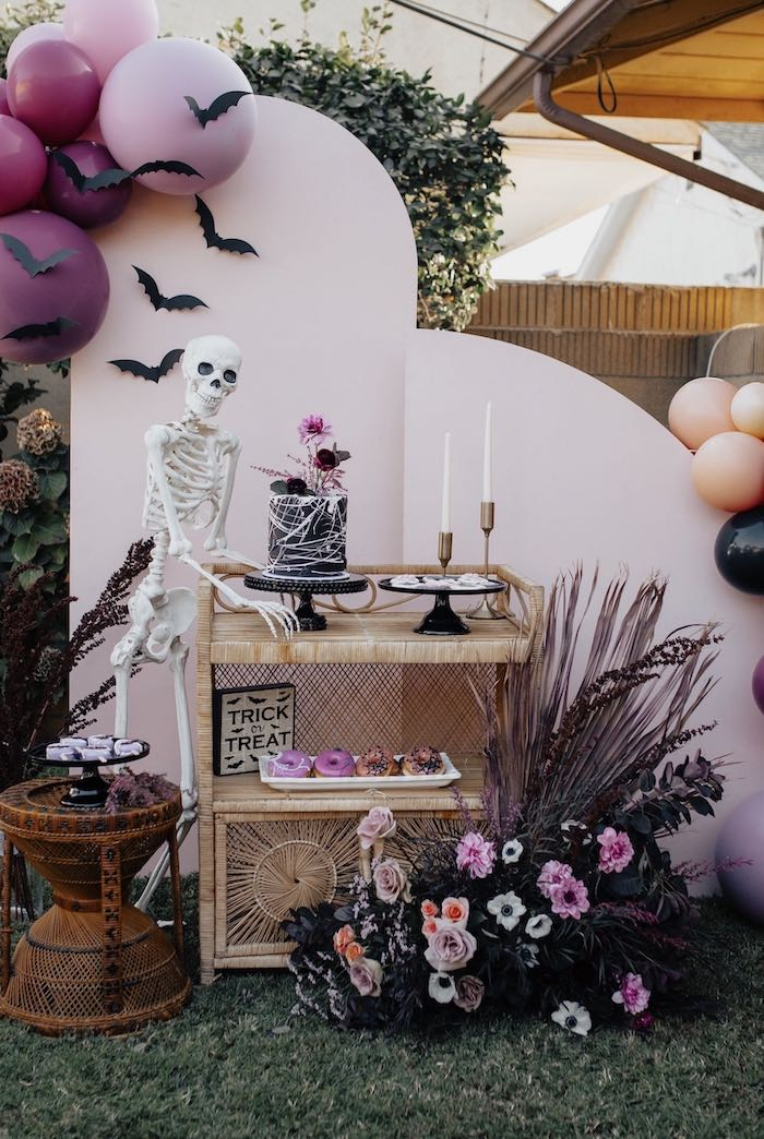 a gorgeous Halloween sweets table with a whimsy black cake with pink blooms and pink glazed donuts served by a skeleton