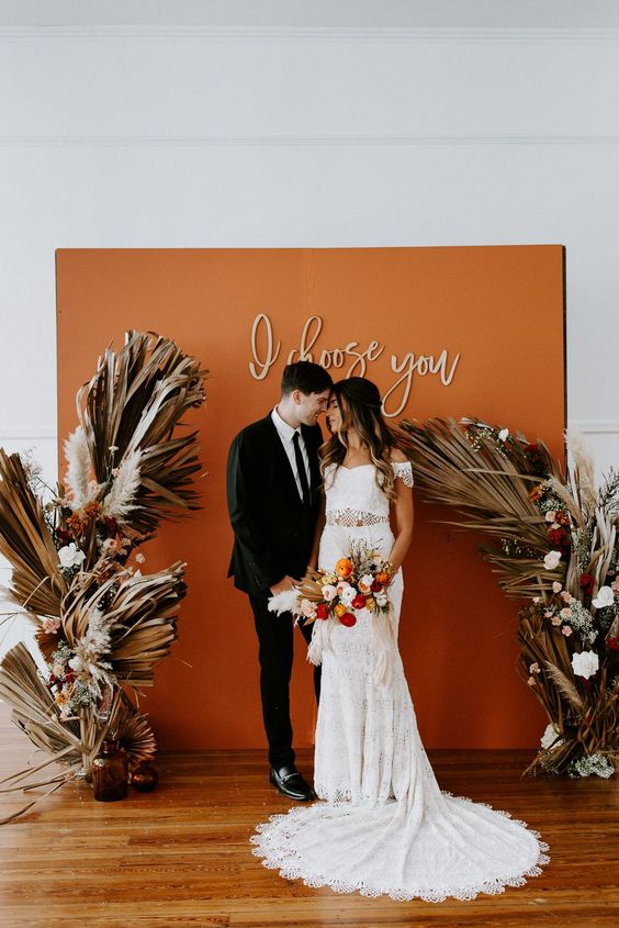 a gorgeous boho fall wedding backdrop in orange, with calligraphy and with dried fronds and white blooms on each side of the backdrop