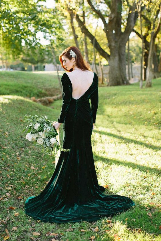 a hunter green velvet mermaid wedding dress with an open back, long sleeves and a train for a fall bride