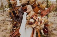 a jaw-dropping boho fall wedding backdrop of dried colorful fronds, leaves, bold blooms of mustard, yellow and some white touches
