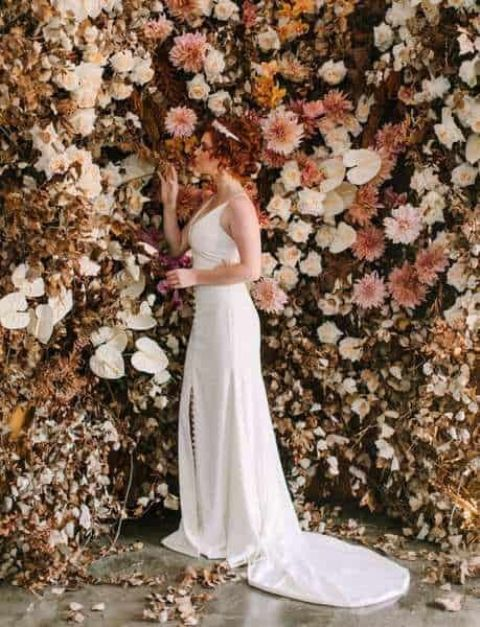 a jaw dropping fall wedding backdrop of blooms, fresh and dried ones and dried leaves is a fantastic idea to rock