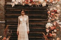 a jaw-dropping wedding backdrop with blush, white, rust and orange blooms, baby's breath, fronds and pampas grass