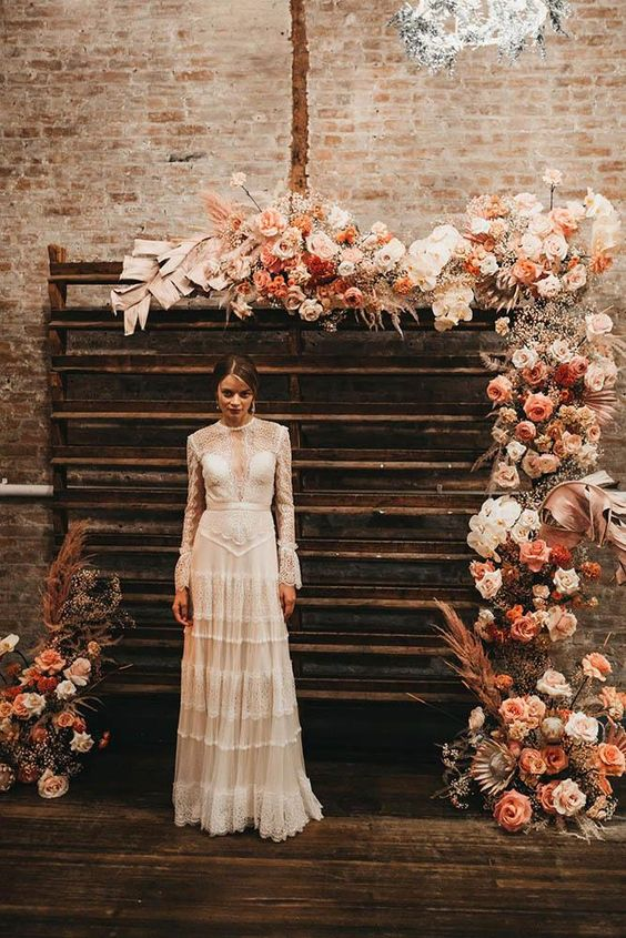 a jaw dropping wedding backdrop with blush, white, rust and orange blooms, baby's breath, fronds and pampas grass