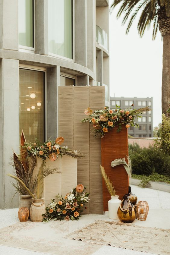 a lovely fall wedding backdrop of rattan, rust and blush blooms, greenery and pampas grass, candles and boho rugs is awesome
