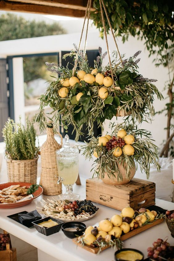 a lovely olive, citrus and cheese food station decorated with foliage, olive greenery and lemons