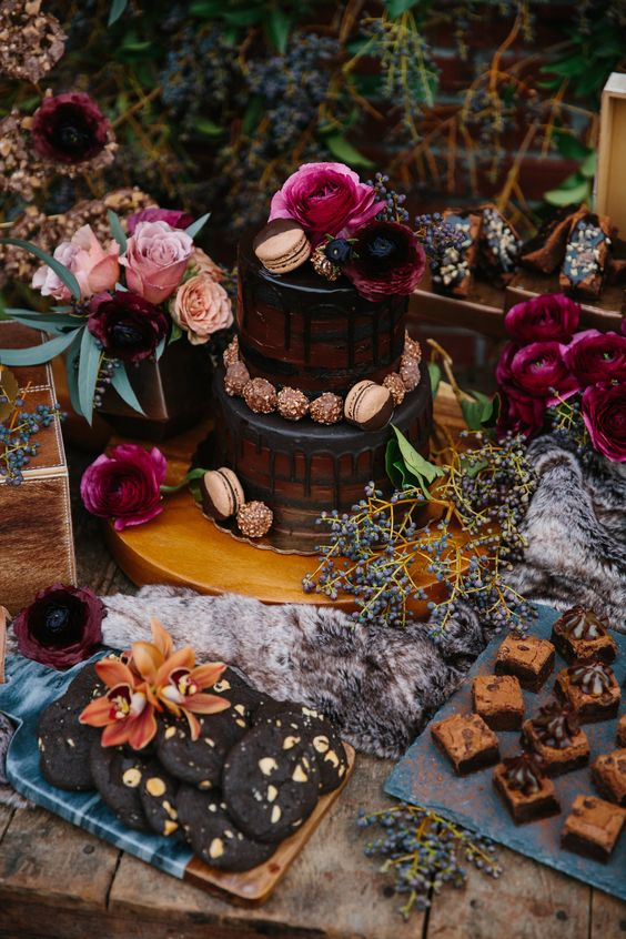 a moody dessert table with a naked cake, chocolate and cookies and fuchsia and pink blooms for a Halloween wedding or shower