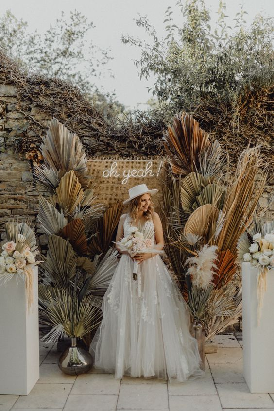 a pretty boho wedding backdrop of burlap, a neon sign and colored dried fronds and pampas grass is amazing