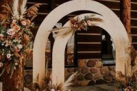 a pretty boho wedding backdrop of two plywood arches, pampas grass, peastel and rust blooms and a boho rug on the floor
