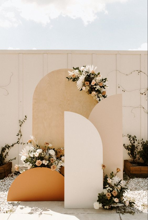 a pretty mid-century modern wedding backdrop in neutrals and rust, with neutral and blush blooms and greenery is amazing for the fall