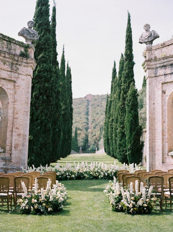 a refined Tuscandy wedding ceremony space with lush white blooms and greenery and tall trees in the backdrop