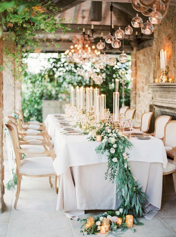 a refined Tuscany wedding reception with tall candles, greenery and white blooms and candles on the floor