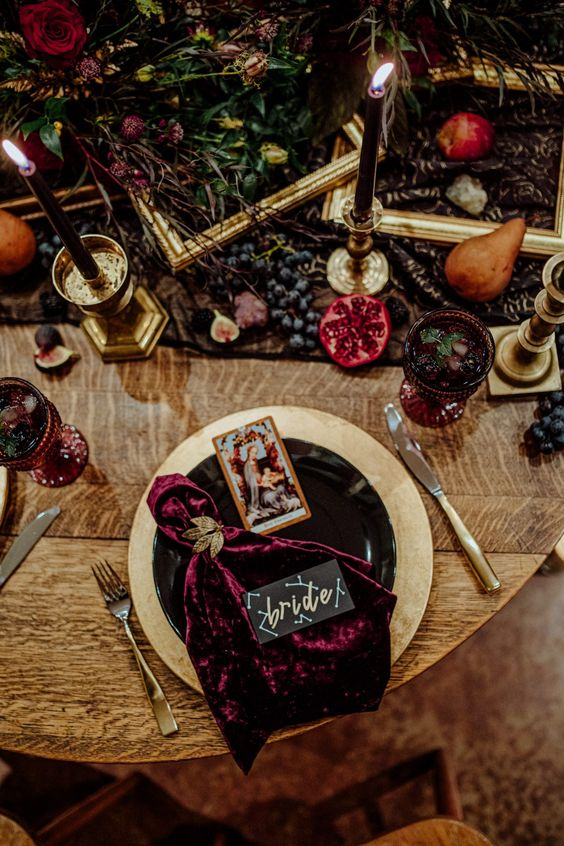 a refined decadent Halloween bridal shower tablescape with gld empty frames, lush jewel-tone blooms, tall black candles and velvet blood-colroed napkins