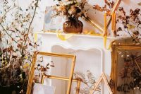 a refined fall wedding backdrop of a faux fireplace, empty frames, fall leaves, candles and a floral arrangement is a gorgeous idea