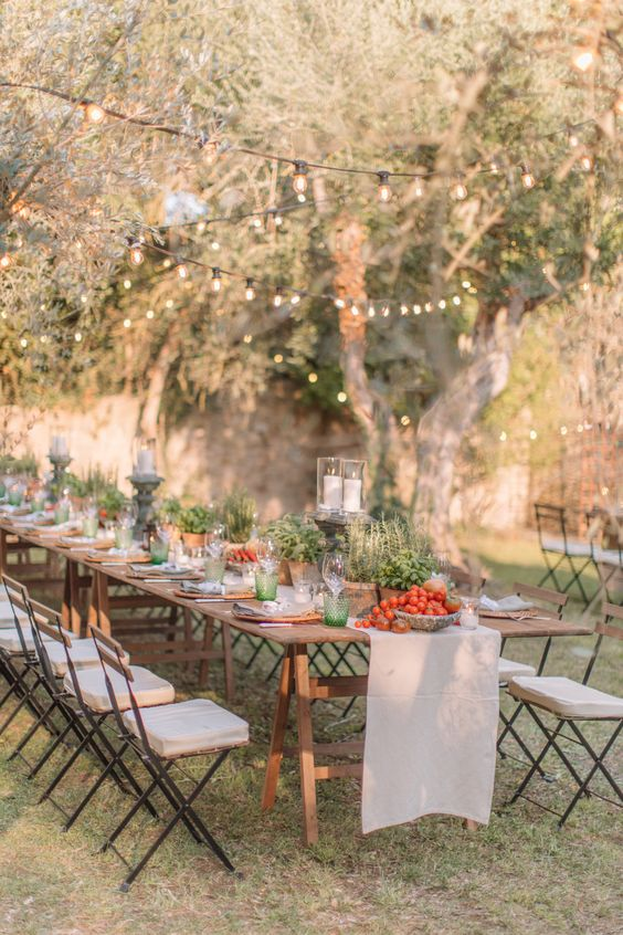 a relaxed Tuscany wedding tablescape accented with potted greenery, with peppers and tomatoes in bowls and pillar candles