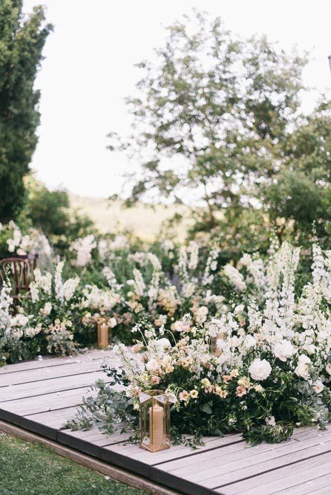 a romantic Tuscany wedding ceremony space with a semi-circular altar with lots of greenery and white and blush blooms