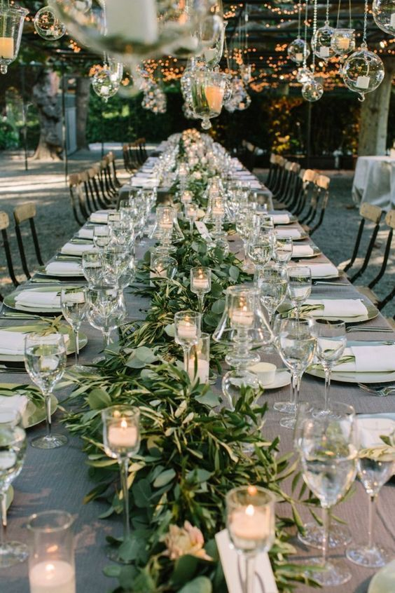 a romantic Tuscany wedding reception with greenery, candles and candle lanterns over the tables