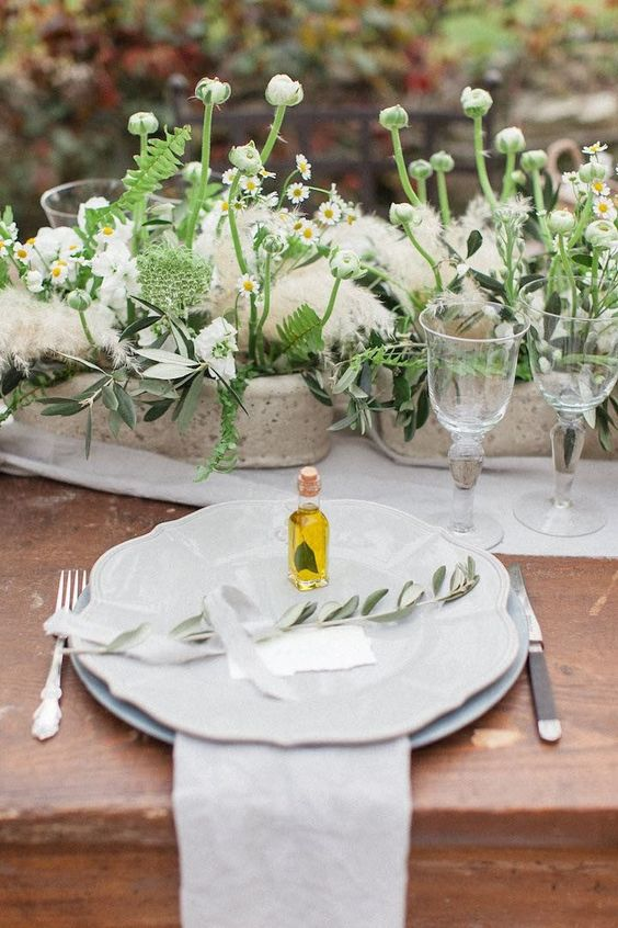 a romantic Tuscany wedding tablescape with potted blooms and leaves, pampas grass and olive oil favors