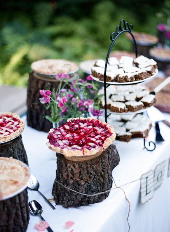 a rustic dessert table styled with tree stumps, a rustic stand with a metal handle and bright blooms in bottles