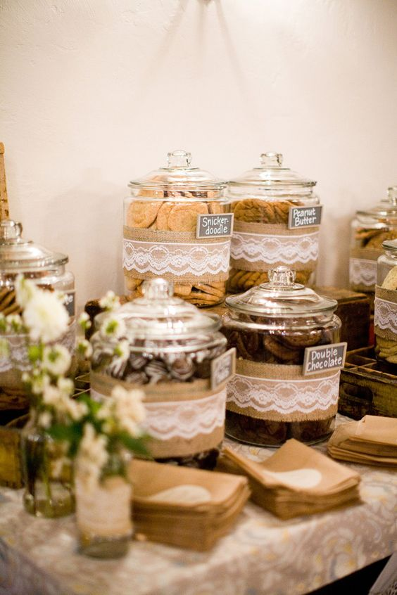 a rustic dessert table with large jars covered in burlap and lace, with neutral blooms and greenery and paper napkins