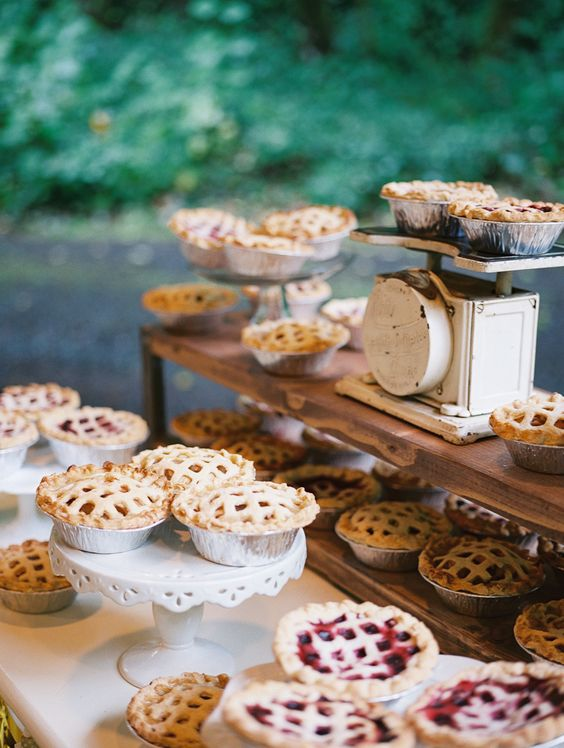 a rustic pie table with mini pies on stands, a wooden shelf with pies and mini scales looks super cute