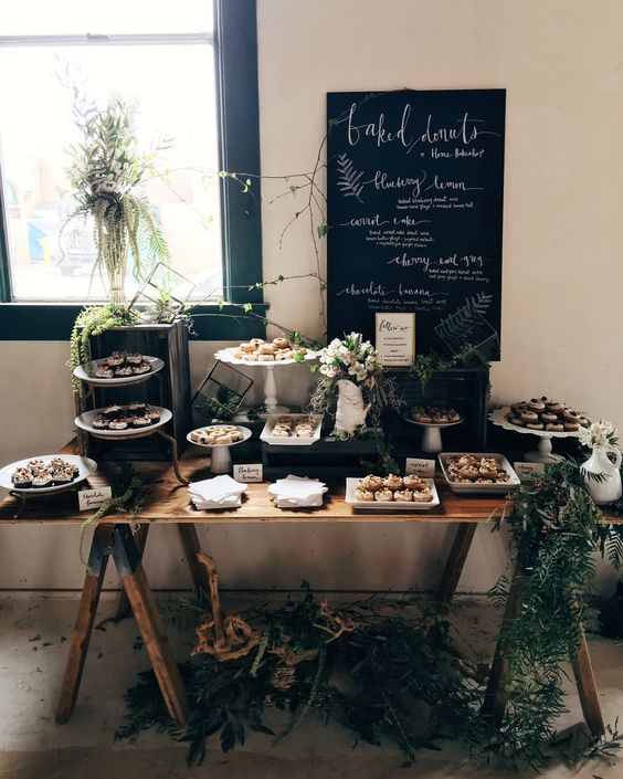a rustic sweets table decorated with greenery and driftwood, a chalkboard and pastel blooms and twigs