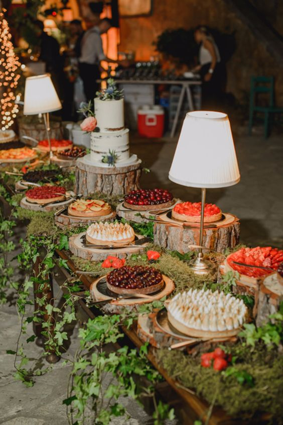 a rustic sweets table topped with moss and cascading greenery, tree stumps and cozy table lamps