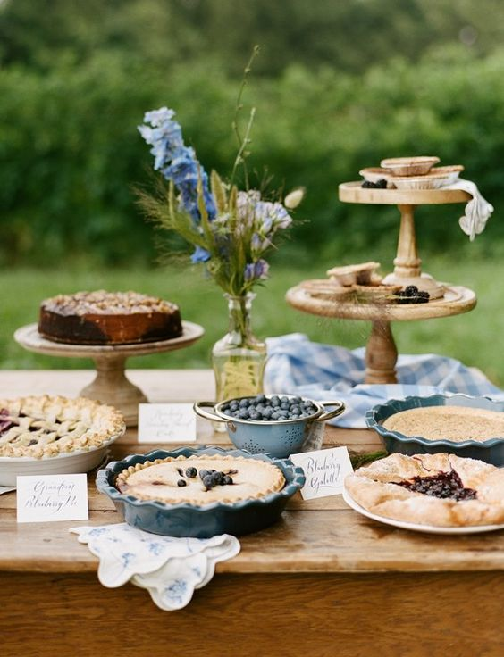 a rustic vintage dessert table with wooden stands, cowls with pies, wildflowers, floral anpkins and berries in a bowl