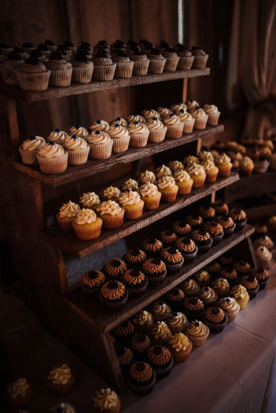 a rustic wooden sweets stand with lots of cupcakes is a very cool and simple idea