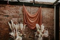 a simple and lovely boho fall wedding backdrop with a rust backdrop and pampas grass plus a boho rug is amazing