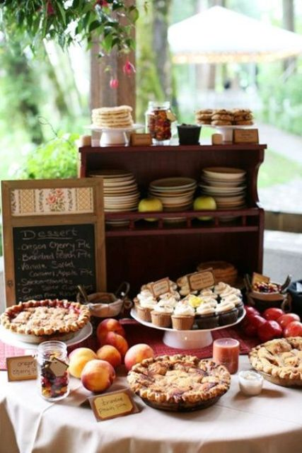 a small and cute rustic dessert table with a wooden stand with plates, cookies and jars, pies and cupcakes on stands and a chalkboard