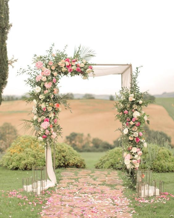 a sophisticated wedding ceremony arch decorated with greenery, neutral and pink blooms and oversized candle lanterns