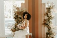 a striped boho fall wedding backrop and dried blooms is a gorgeous solution for a boho fall wedding or a mid-century modern one