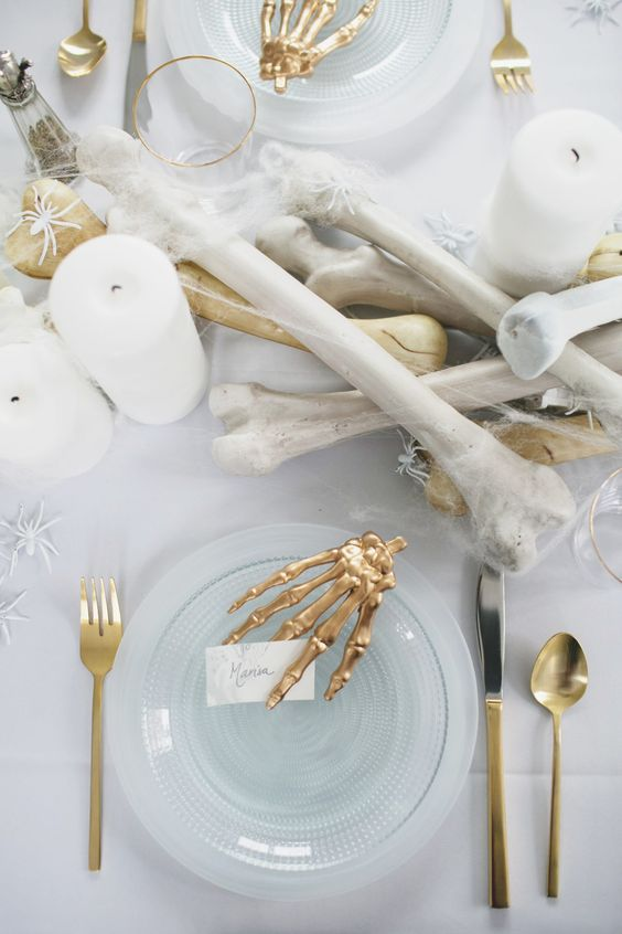 a stunning all-white tablescape with faux bones and spiders and gilded touches will be a refined and cool idea for a Halloween bridal shower