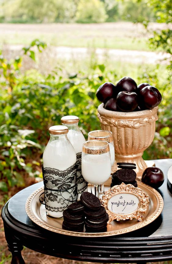 a stylish Tim Burton-inspired dessert table with milk, cookies and dark apples wows for a Halloween wedding or bridal shower