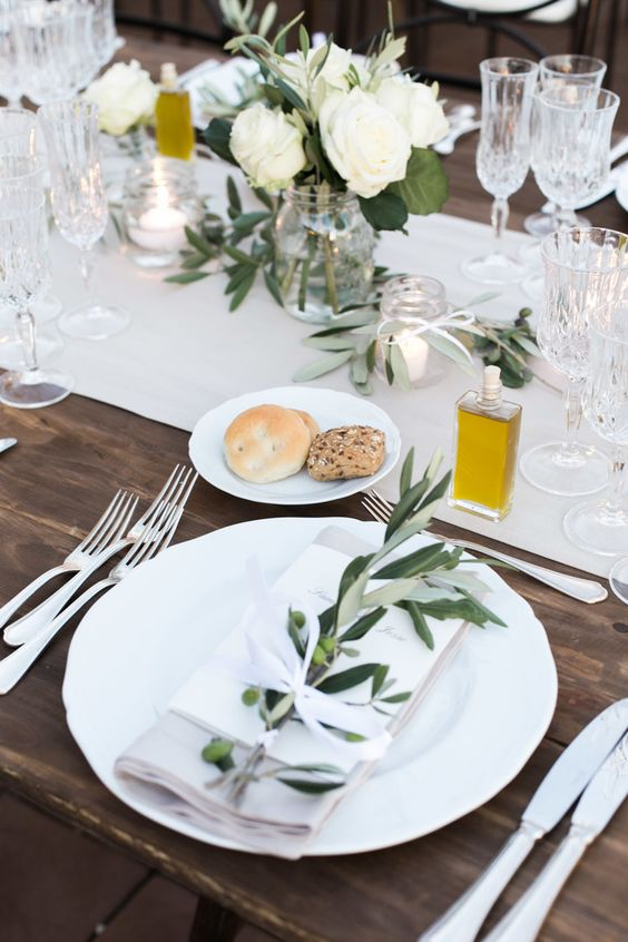 a stylish Tuscany wedding tablescape with neutral linens, neutral blooms and greenery, olive oil as favors and fresh bread