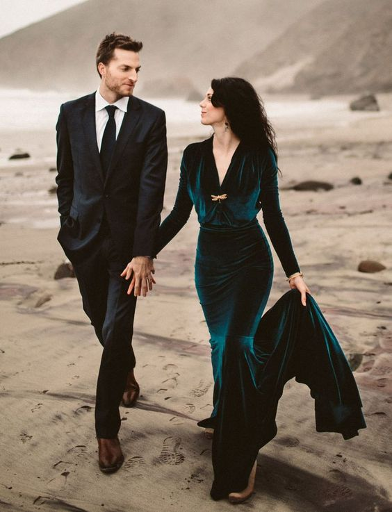 a teal velvet mermaid wedding dress with a V-neckline and long sleeves plus a train for a fall wedding