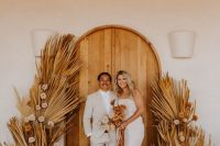 a very simple boho fall wedding backdrop of wooden doors, dried fronds and blush blooms on each side is a lovely idea for a fall boho wedding