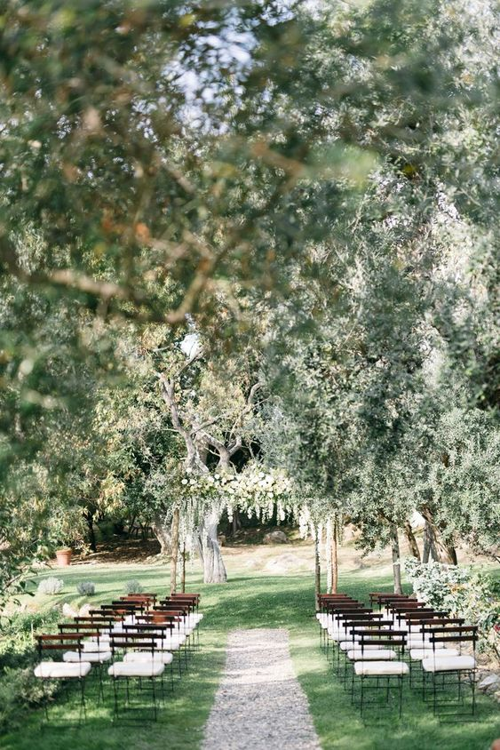 a wedding ceremony in an olive grove, with a white floral arch and simple white chairs