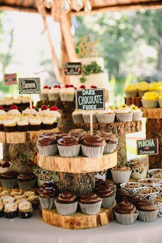 a wedding cupcake bar with wood slice stands and chalkboard tags is a cozy rustic idea for your fall wedding