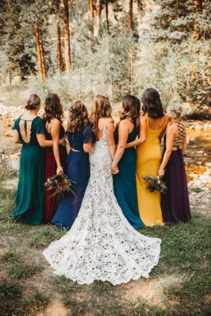 amazing mismatching maxi bridesmaid dresses in emerald, teal, electric blue, deep purple and marigold for a trendy fall bridal party look