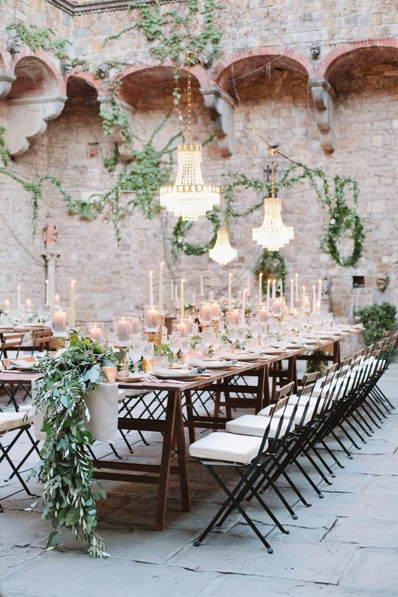 an amazing Tuscany wedding reception with lots of candles and greenery, chandeliers over the tables