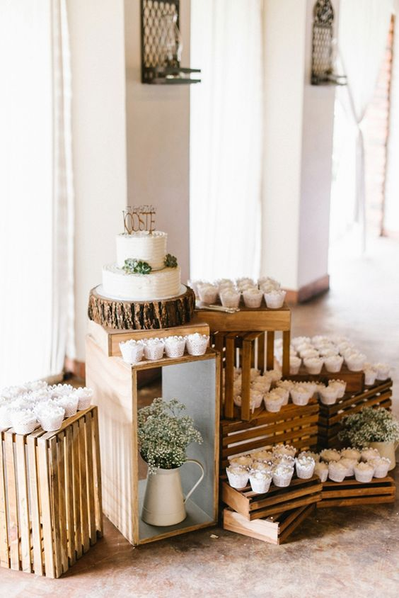 an easy rustic sweets display of crates, with baby's breath and cupcakes and a cake with succulents
