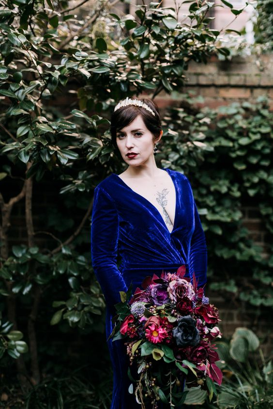 an electric blue velvet wedding dress with draperies and long sleeves plus a plunging neckline and a crystal headpiece