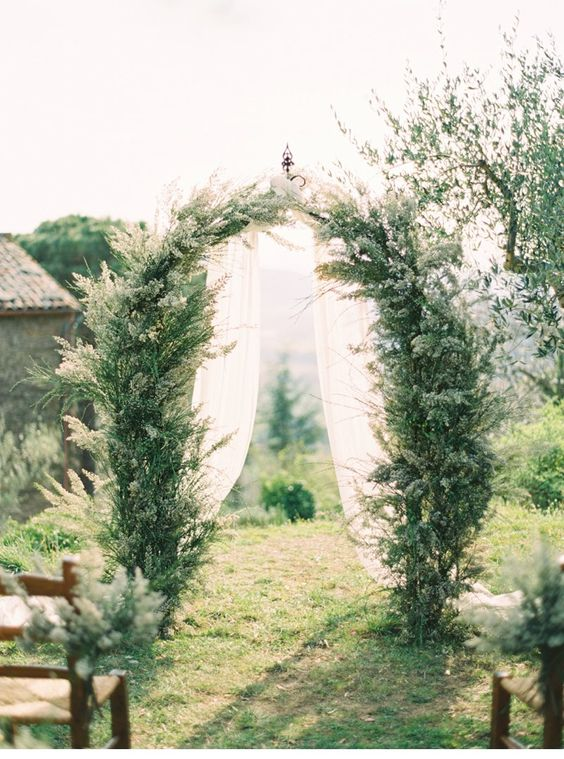 an ethereal Tuscany wedding arch covered with greenery and with white airy fabric is beautiful