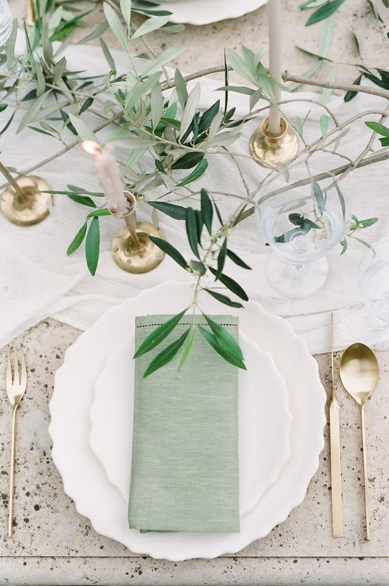 an ethereal wedding tablescape with greenery, blush candles in gold candleholders, green napkins and gold cutlery