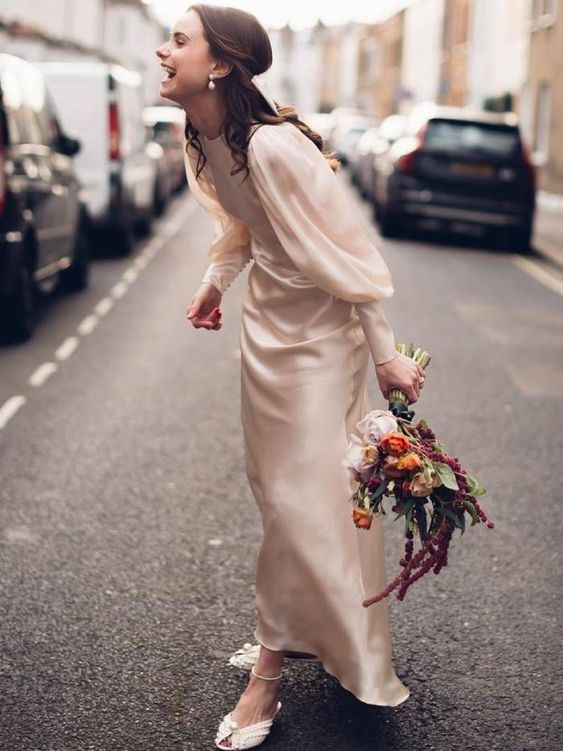 an ivory silk sheath wedding dress with a high neckline, puff sleeves on buttons and white embellished shoes