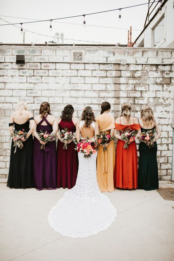 beautiful mismatching bridesmaid dresses in burgundy, deep purple, orange, marigold, black are gorgeous for the fall