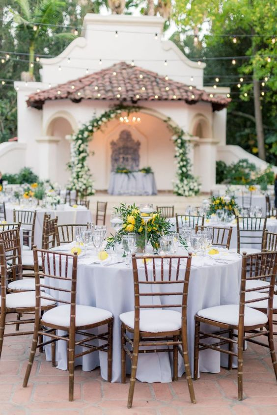 chic and elegant wedding tablescapes done with lemons and greenery and lemon centerpieces are adorable