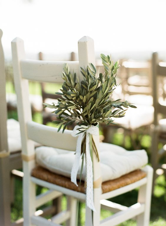 highlight the wedding chairs with olive branches with a lace bow